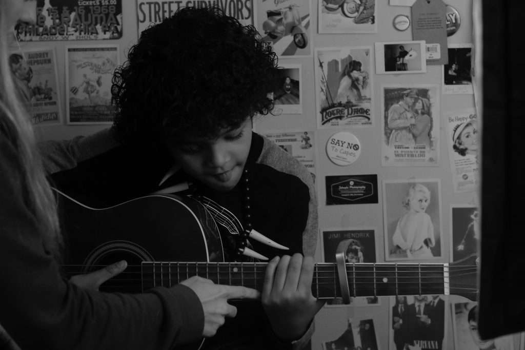 photo of a young boy during guitar lessons at Crossroads Collective. This music centre in Langley offers voice, piano and guitar lessons.