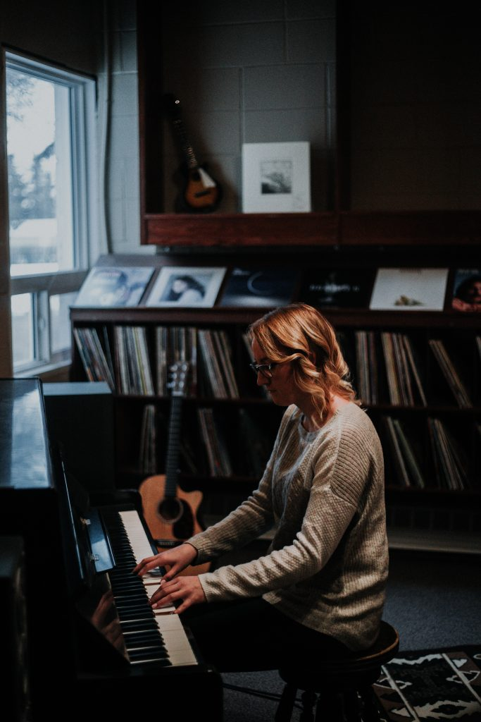 Woman playing the piano during Crossroads Collective music lessons in Langley.